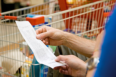 Shopper reviewing receipt, cropped - p623m1487554 by James Hardy