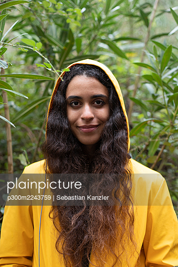Close-up of female hiker wearing yellow raincoat standing against plants in forest - p300m2243759 by Sebastian Kanzler
