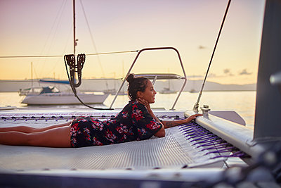 Serene young woman relaxing on catamaran net at sunset - p1023m2016845 by Trevor Adeline