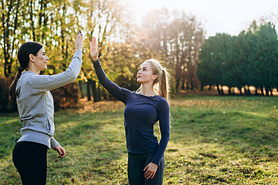 Two girls in the park are exercising and clapping their hands. - p1166m2171863 by Cavan Images