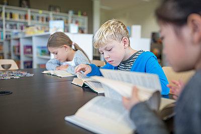 Pupils reading books on table in school break room - p300m2005297 by Fotoagentur WESTEND61
