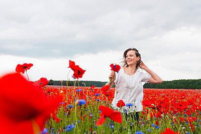 Happy beautiful woman walking on poppy field against cloudy sky - p300m2197486 by Daniel Ingold