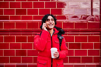 Smiling young man holding disposable coffee cup while talking on mobile phone against wall - p300m2264782 by Angel Santana Garcia