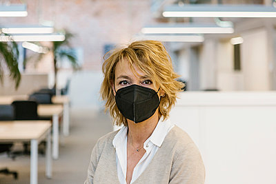 Businesswoman wearing protective face mask in office during pandemic - p300m2282707 by Xavier Lorenzo