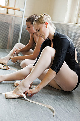 Ballerinas putting on ballet slippers - p9245504f by Image Source