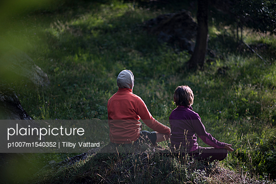 People meditating in the grass of a field at sunrise - p1007m1540352 by Tilby Vattard