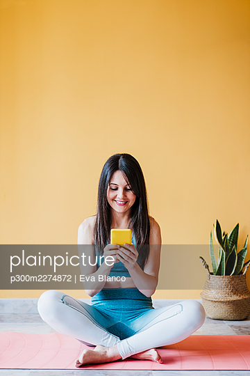 Beautiful woman sitting with cross legged using smart phone at home - p300m2274872 by Eva Blanco