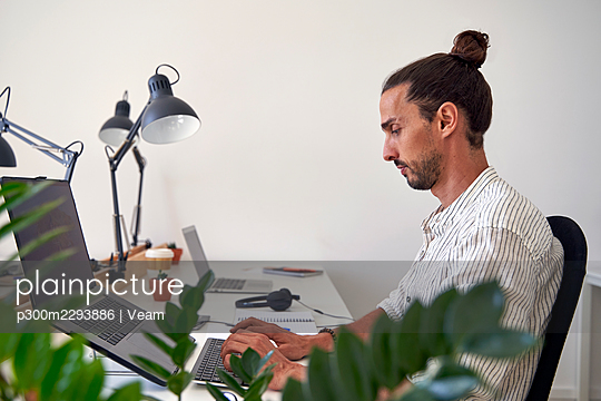 Male professional working on laptop at office - p300m2293886 by Veam