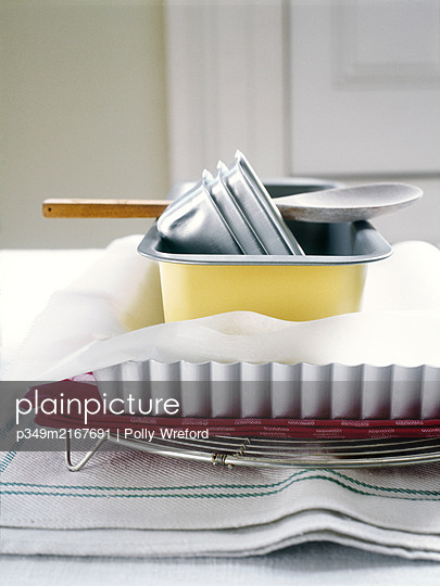 Assorted cake tins and wooden spoon - p349m2167691 by Polly Wreford