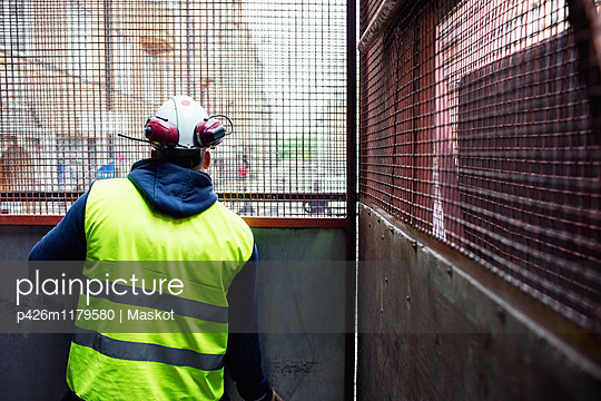 Rear view of construction worker looking through metal grate - p426m1179580 by Maskot