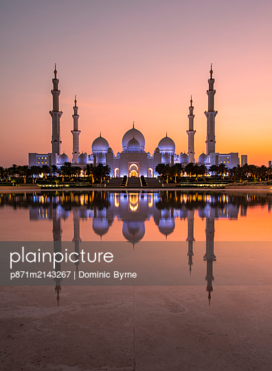 Sheikh Zayed Mosque (the Grand Mosque) reflected in a pool of water at sunset in Abu Dhabi, United Arab Emirates - p871m2143267 by Dominic Byrne