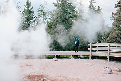 Side view of boy standing on pier over hot spring at Yellowstone National Park - p1166m2034941 by Cavan Images