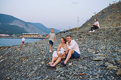 Father, pregnant mother, elder daughter and two little sons on stony beach - p1363m1590985 by Valery Skurydin