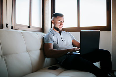 Smiling businessman working on laptop while sitting on sofa at home - p300m2256938 by Miguel Frias