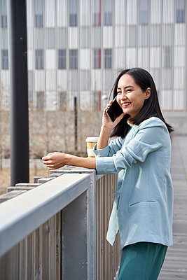 Smiling businesswoman talking on mobile phone while leaning on railing - p300m2277685 by Veam