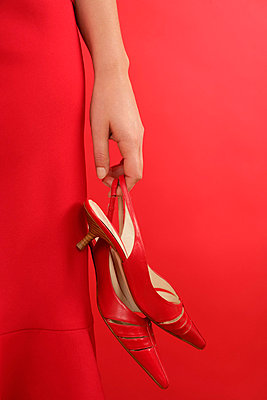 Close-up of hand holding pair of red shoes - p4901771 by STOCK4B