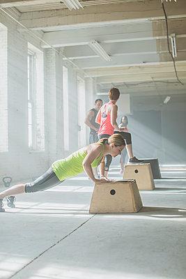 Athlete doing push-ups on platform in gym - p555m1411978 by John Fedele