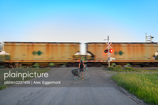Cyclist waiting for train ahead to pass, Ontario, Canada - p924m2237499 by Alex Eggermont