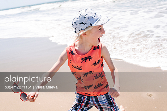 Boy on beach as sea waves come towards him - p924m2271151 by Viara Mileva