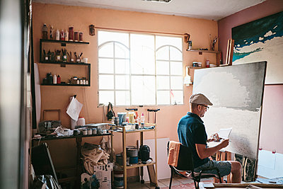 Mid adult man working as painter with brush and canvas in his studio - p1166m2078301 by Cavan Images