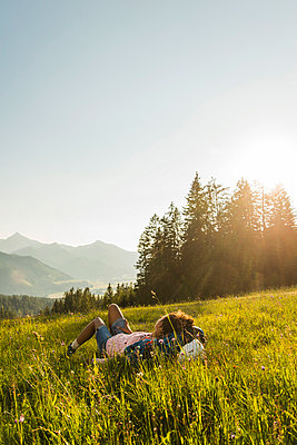 Austria, Tyrol, Tannheimer Tal, young woman lying on alpine meadow - p300m1052921f by Uwe Umstätter