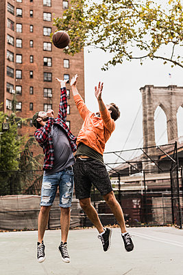 USA, New York, two young men playing basketball on an outdoor court - p300m1192253 by Uwe Umstätter