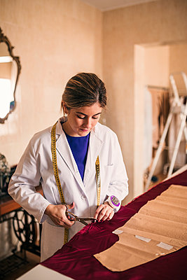 Female dressmaker cutting maroon silk fabric with scissor at workshop - p300m2293492 by LUPE RODRIGUEZ
