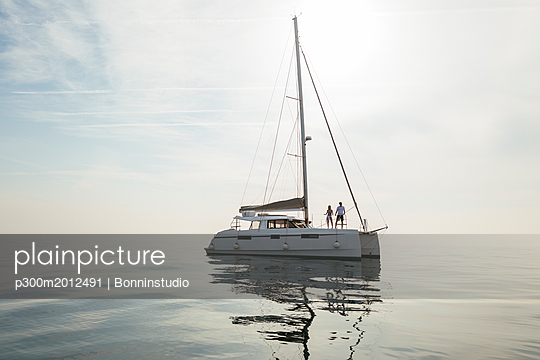 Couple setting off for a sailing trip on a catamaran - p300m2012491 von Bonninstudio