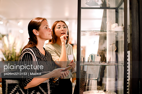 Saleswoman showing earrings to female customer at fashion store - p426m2213153 by Maskot