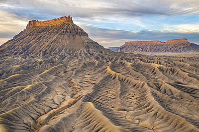 Aerial view of barren desert landscape with buttes and mesas - p1166m2107899 by Cavan Images