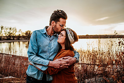 hip husband kissing smiling wife near a lake in Colorado - p1166m2208504 by Cavan Images