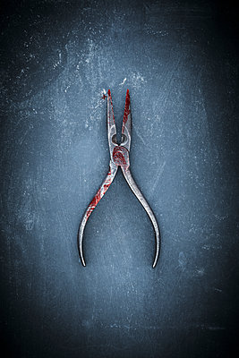 An old pair of long nosed pliers with blood and bloody fingerprints, on a dark background - p1302m2089435 by Richard Nixon