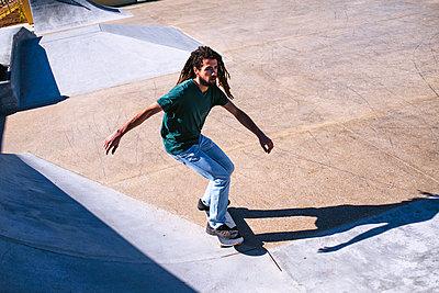 Young man with dreadlocks skateboarding in a skatepark - p300m1120684f by Kiko Jimenez