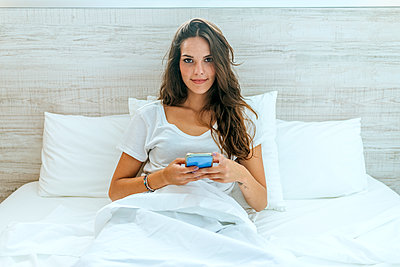 Portrait of young woman with cell phone in bed at home - p300m2132068 by Kiko Jimenez