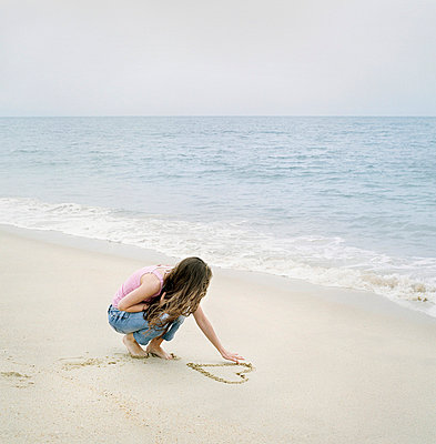 Young woman drawing a heart shape on sand on the beach - p3741539 by Karin Smeds