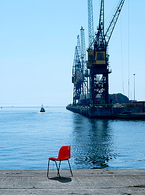 Empty chair on shipyard dock - p42916986 by Charlie Fawell