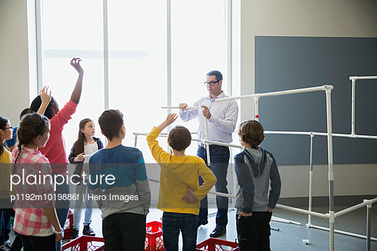 Teacher and students assembling model pipeline - p1192m1019886f by Hero Images