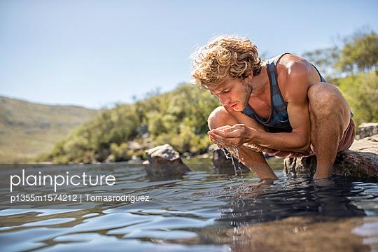Junger Mann erfrischt sein Gesicht mit Wasser - p1355m1574212 von Tomasrodriguez