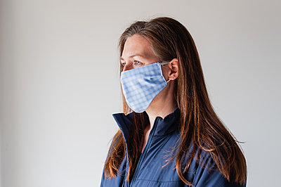 Woman wearing homemade cloth face mask during Covid 19 pandemic. - p1166m2174106 by Cavan Images