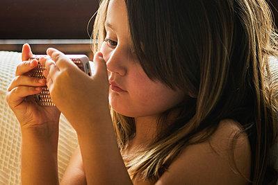 Little girl looking at her smart phone - p1418m2008102 by Jan Håkan Dahlström