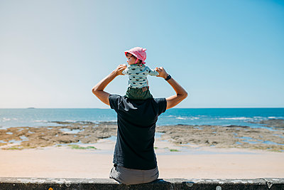 Back view of father with little daughter on his shoulders on the beach - p300m2005616 von Gemma Ferrando