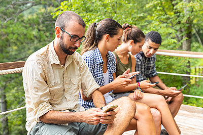 Italy, Massa, hikers in the Alpi Apuane mountains looking at their smartphones and sitting on a bench - p300m2063051 by William Perugini
