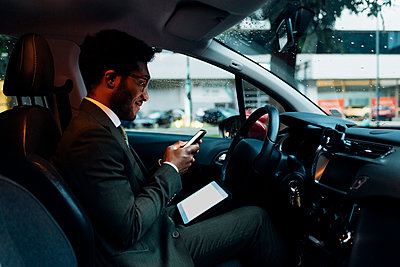 Young black businessman sitting car stuck traffic using device - Milan, Lombardy, Italy - rush hour, technology, entertainment concept - p300m2294079 von Eugenio Marongiu