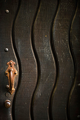 Detail old rusted door handle on dark wooden door - p5551749f by Eric Hernandez