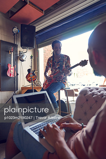 Musicians with laptop and electric guitar in garage recording studio - p1023m2190247 by Trevor Adeline