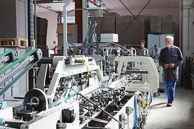 Factory workers machine in cardboard factory - p429m942791f by Judith Haeusler