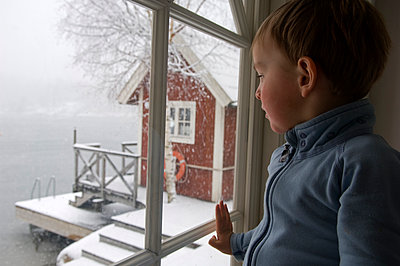 A child looking out a window a winter day - p575m1075067f by Fredrik Schlyter