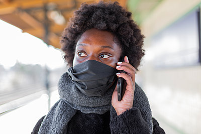 Germany, Berlin, Young dark-skinned woman using smartphone on the train platform - p975m2247761 by Hayden Verry