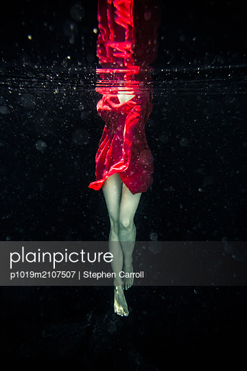 Underwater View of Legs of Woman in Red Dress - p1019m2107507 by Stephen Carroll