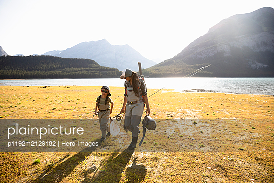 Mother and son fly fishing at sunny, scenic lake - p1192m2129182 by Hero Images